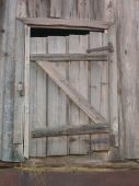 Grey wooden door to hayloft. Taken one winter day. poster
