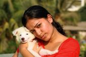A smart Indian girl with her soft white puppy. poster