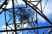 Abstract high-voltage tower on blue sky background poster
