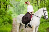 Cheerful girl riding horse in the forest poster