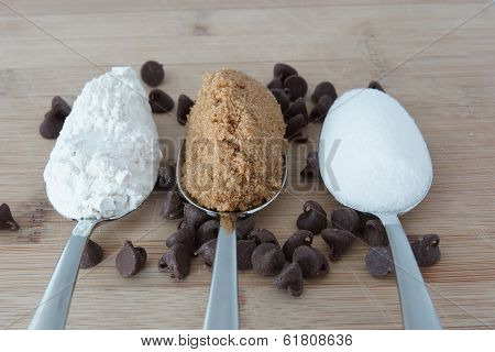 Three Spoons With The Ingredients To Make Chocolate Chip Cookies