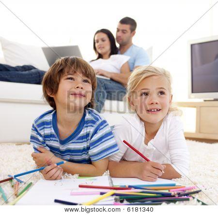 Kinder Malerei im Wohnzimmer und Eltern auf sofa
