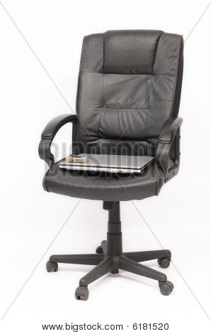 Laptop and mobile phone on the black chair