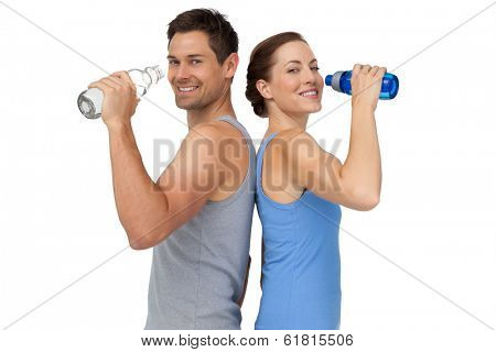 Portrait of a happy fit young couple with water bottles over white background
