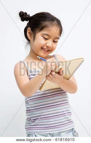 Beautiful little Asian girl writing