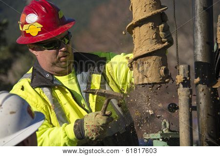 Foreman Hammering On A Drill Rig