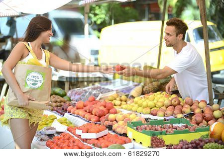 Greengrocer owner of a small business at an open street market, handing out a fruit to a consumer, carrying a shopping bag with 100% organic certified label.