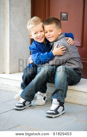 Happy brother sitting on door steps and embracing
