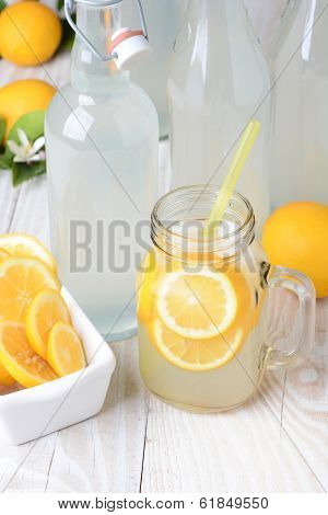 Old fashioned sparkling lemonade shot from a high angle. Vertical format on a rustic wooden farmhouse style table.