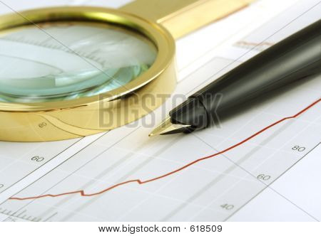 A Pen And A Magnifying Glass Focusing On A Chart.