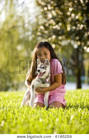 Pretty young Asian girl hugging Alaskan Klee Kai puppy sitting on grass poster