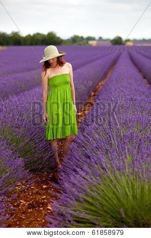 Romantic Woman In Green Dress And Hat Standing In Lavender Field In Provence, France.