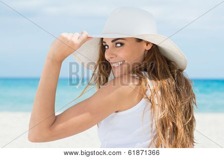 Happy Young Woman Looking At Camera Wearing White Sunhat At Beach