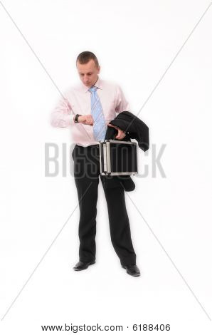 Young walking businessman looking at a watch