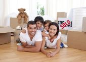 Happy family lying on floor after buying new house poster