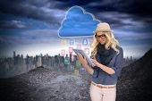 Digital composite of stylish blonde using tablet pc with app icons and cloud poster