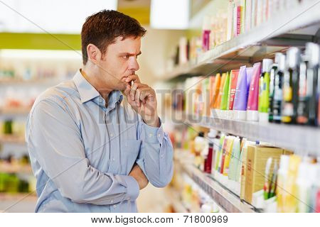 Pensive man in supermarket making a sustainable shopping decision