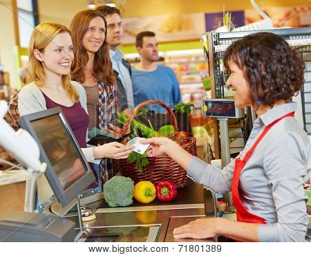 Smiling woman paying cash with Euro money bill at supermarket checkout