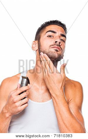 young handsome man in white shirt trimming his beard with a trimmer poster