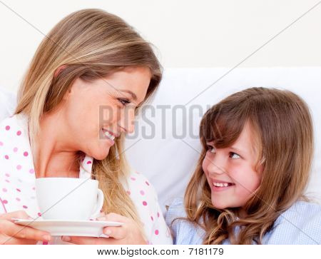 Attentive Mother And Her Daughter Drinking Coffee Lying In Bed