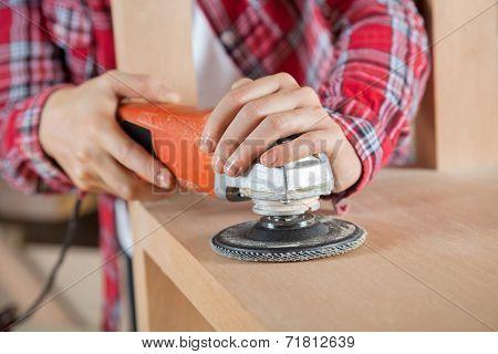 Female carpenter's hands using sander on wooden shelf in workshop