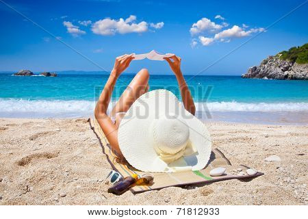 Beautiful woman reading book on Sarakiniko beach. Just 8km outside the village Parga after Agia village in Syvota area, Greece.