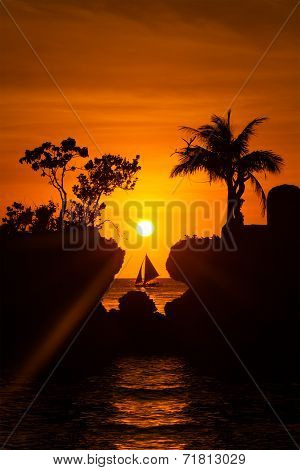 Sailboat At Beautiful Sunset Above The Tropical Sea. Silhouette Photo.