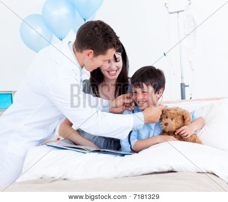 Smiling Doctor Playing With A Little Boy And His Mother