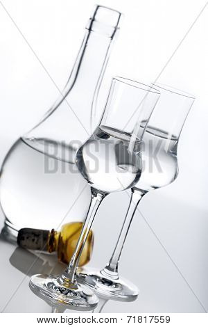 Clear spirit in two glasses and carafe, tilted view