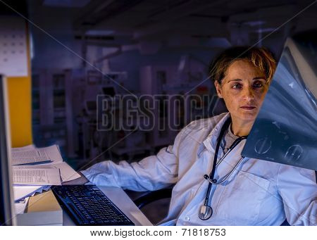 Tired Doctor Looking X Ray  At Night Duty
