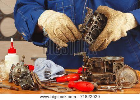 Master repairing old car engine carburetor