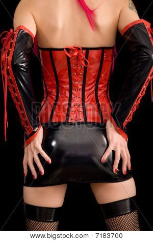 Woman dressed in dominatrix clothes from back isolated on black background poster