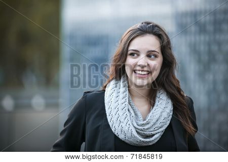 Candid portrait of young brunette woman smiling and looking to side with copy space