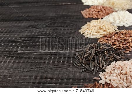 Frame made of colorful varieties of whole grain rice in a rustic wooden surface background