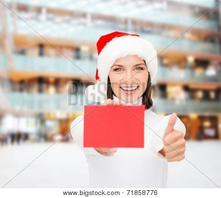 christmas, holdays, people, advertisement and sale concept - happy woman in santa helper hat with blank red card showing thumbs up gesture over shopping center background