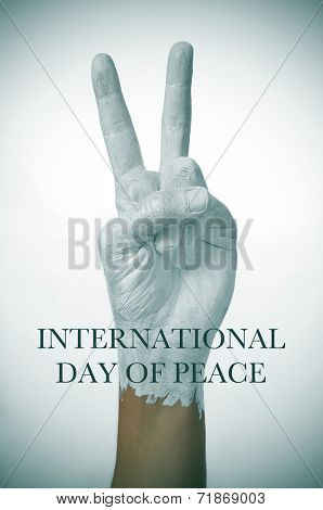 a man hand painted in white giving the V sign, as symbol of peace, and the sentence international day of peace
