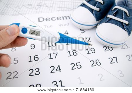 Electronic Thermometer In Fertility Concept On Calendar