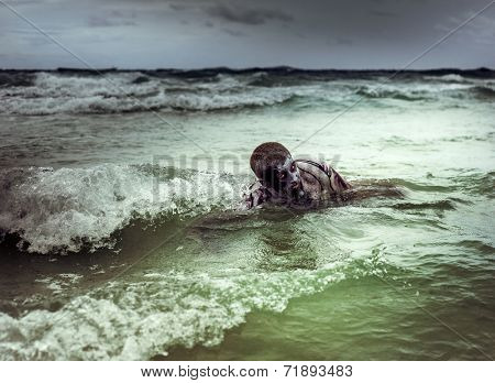 young man with a zombie body painting, covered with blood swimming in the ocean  (halloween topic)