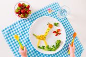 Healthy vegetarian lunch for little kids vegetables and fruit served as animals corn broccoli carrots and fresh strawberry helping children to learn eating right and clean child's hands holding spoon poster