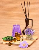 Aromatherapy accessories: floral petals bottles filled with aromatic oils incense sticks candle on wooden surface poster
