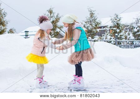 Adorable little girls skating on ice rink outdoors in winter snow day
