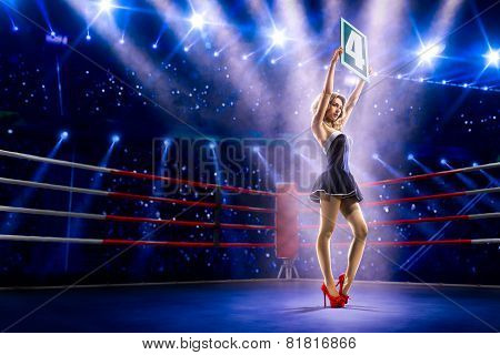 Boxing ring girl  is holding the number