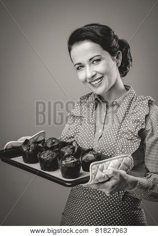 Smiling vintage woman holding a baking tray with chocolate home made muffins poster