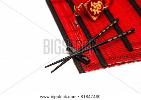 Black Chopsticks On Red Bamboo Mat. Chinese New Year Ornament