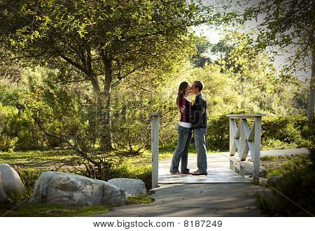 Caucasian Couple Kissing On Wooden Bridge