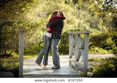 Caucasian Couple Hugging On Wooden Bridge