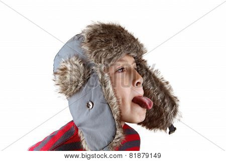 Boy in furry hat poking out tongue