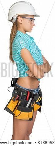 Woman in hard hat, tool belt and protective glasses