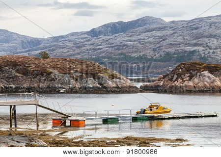 Rural Norwegian coastal landscape. Small motor boat stands moored near floating pier poster