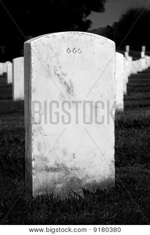 Headstone in a graveyard with evil 666 engraving poster